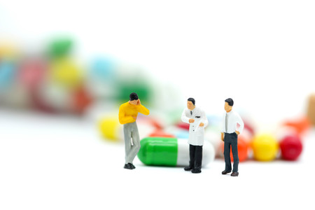 Miniature people: doctor stand with drug,pills,capsules Healthy and medicine concept.
