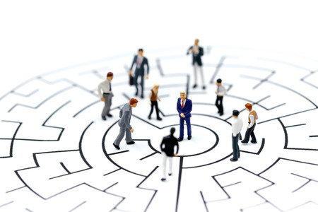 Miniature people: Businessman standing on start point of maze using as background business concept.