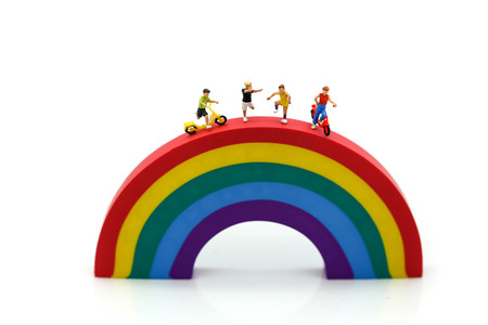 Miniature people : children cycling playground in city park with rainbow background,Play and learn concept.