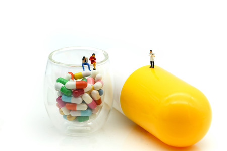 Miniature people : Doctor and patient with Capsule pill and  alarm clock for warning about eating medicine time,Drug resistance concept