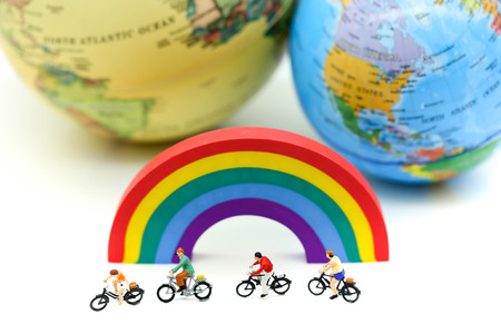Miniature people : Travelers riding bicycle on rainbow with world map,travel concept.