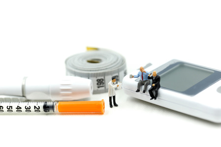 Miniature people : Doctor and patient with Glucose meter diabetes test and Syringe with measuring tape,concept of diabetes, healthy lifestyles and nutrition Stock Photo