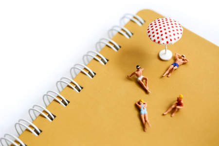 Miniature people : man and woman sunbathing relaxing on beach, ocean view,Beach vacation concept.