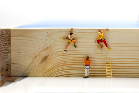 Miniature people. : climbing ladders to get to the top of the position wooden Stock Photo