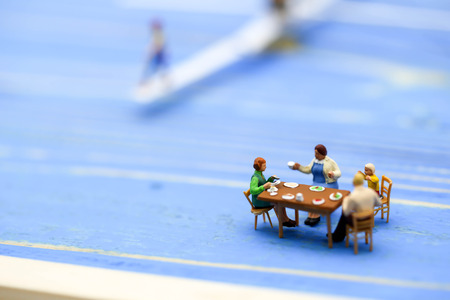 Miniature people : Families are celebrating , eating together happily.
