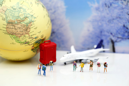 Miniature people : Traveler backpack with airplane,worldmap,luggage of snow winter background.