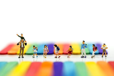 Miniature people : A group of young children getting on the schoolbus with Colorful ice cream sticks background. Stock Photo