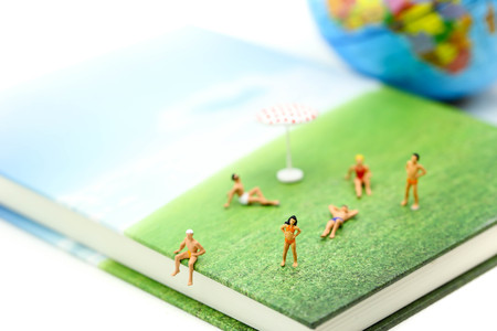 Miniature people wearing swimsuit relaxing on book and world map background,holiday, vacation concept.