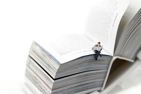Persone in miniatura: seduto sul libro utilizzando come concetto di educazione e background sociale.