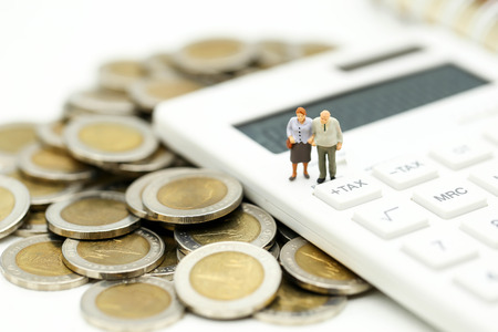 Miniature people : Couple oldman standing with Calculator,business,tax concept. Stock Photo - 106928500