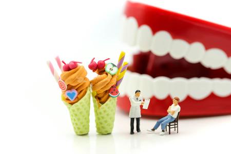 Personnes miniatures : dentiste et équipe médicale devant les dents avec une glace patiente et sucrée, concept médical de soins de santé.