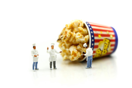 Miniature people : Chef and friend with popcorn. Stock Photo