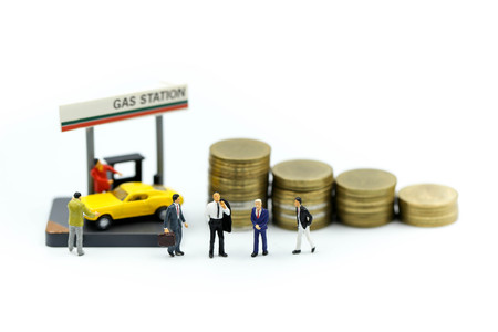 Miniature people : Businessman On Gas Station with coins,business gas station economy concept.