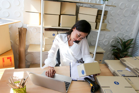 Young asian girl is freelancer Start up small business owner writing address on cardboard box at workplace,Shipping shopping online small business entrepreneur SME or freelance Stock Photo
