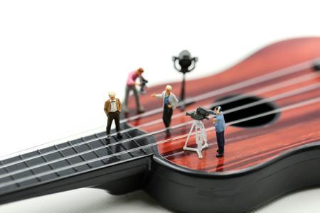 Miniatuurmensen: regisseur, personeel en acteurs op de set van de videozanger met gitaar, productiemuziekconcept.