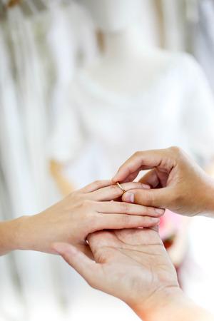 Pareja de novios cogidos de la mano y ponerle un anillo de bodas, Foto de archivo