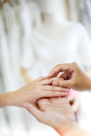 Wedding couple holding hands and put her a wedding ring, Фото со стока