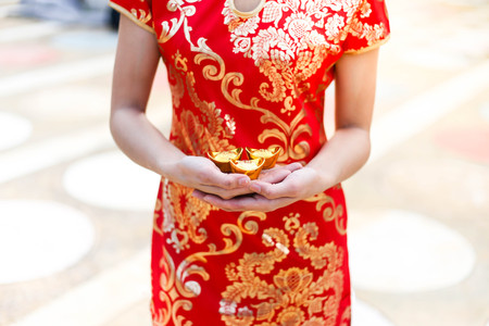 Beautiful asian woman wear cheongsam and holding gold bars as gifts for the Chinese New Year for you. Happy Chinese New Year festival.