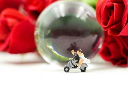 Miniature people : Couple of love riding the motorcycle on The Globe with rose background.