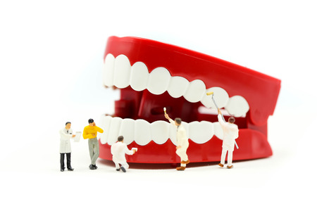 Miniature people : clean tooth or dental model with Dentist examining a patients teeth ,using for concept of Dentists Day.