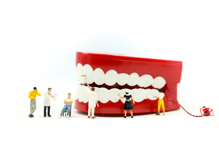 Miniature people : clean tooth or dental model with Dentist examining a patient's teeth ,using for concept of Dentist's Day. Reklamní fotografie