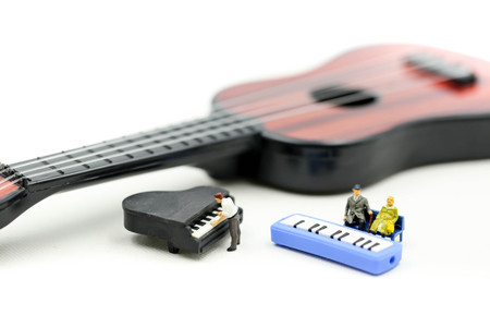 Miniature people: man play mini piano with  sitting on acoustic guitar. time of relax or music relax concept.