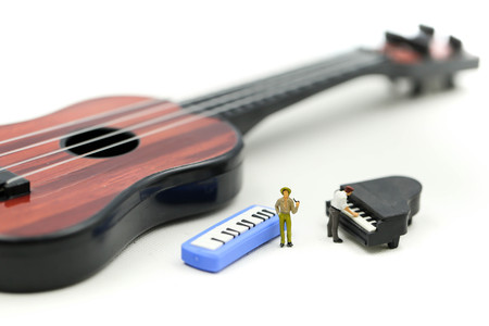 Miniature people : man play mini piano with  sitting on acoustic guitar. time of relax or music relax concept. Standard-Bild - 122326351