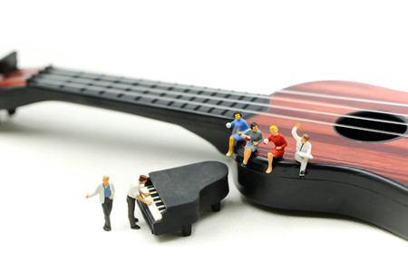 Miniature people : man play mini piano with  sitting on acoustic guitar. time of relax or music relax concept.