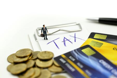 Miniature people : businessman with credit card and stack coins of tax commitment, agreement, investment, business and partnership concept