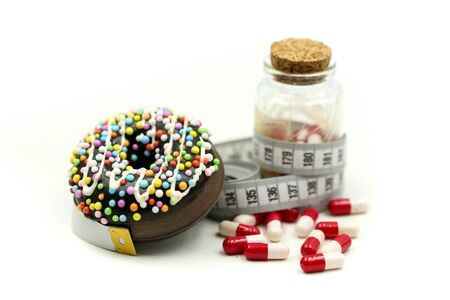 Doughnut tying by measuring tape and pills of medicine, dietary for slim shape concept Archivio Fotografico - 133240567