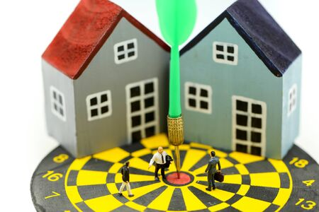 Miniature people : Businessman standing at the center of dartboard with house as business goal achievement Property Business and Strategy Planning concept.