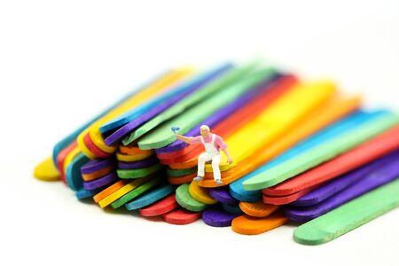 Miniature people : worker painting on Colorful ice cream sticks Archivio Fotografico - 132747933
