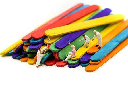 Miniature people : worker painting on Colorful ice cream sticks