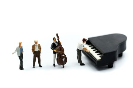 Miniature people : pianist playing piano and Violinist Man, playing musical instrument concept. Фото со стока - 129882103