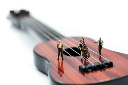 Miniature people : pianist playing piano and Violinist Man,playing musical instrument concept. Фото со стока - 129882102
