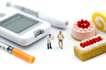 Miniature people : Doctor and patient with Glucose meter diabetes test and Syringe with measuring tape, concept of diabetes, healthy lifestyles and nutrition