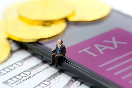 Miniature people : Oldman  Bitcoin Crypto Currency with TAX message and dollars money, Determining the tax law of digital money Concept