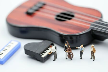Miniature people : pianist playing piano and Violinist Man, playing musical instrument concept.