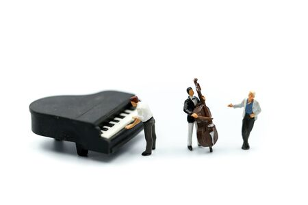 Miniature people : pianist playing piano and Violinist Man, playing musical instrument concept. Фото со стока - 129885112