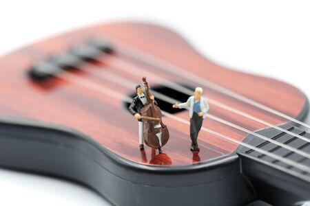 Miniature people : pianist playing piano and Violinist Man, playing musical instrument concept. Фото со стока - 129885305