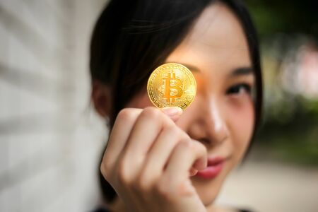 Selective of focus with Businesswoman holding the bitcoin gold coin