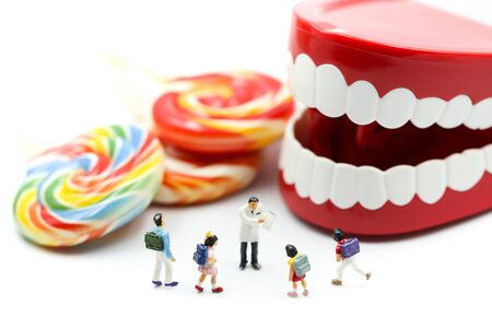Miniature people : Doctor dentist speaks about student and children with desserts
