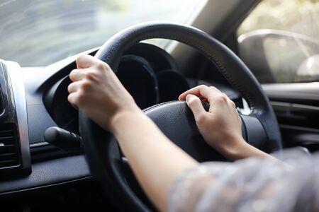 Beide Hände der Frau, die ein Rad trägt, das ein Rechtslenkerauto fährt. Standard-Bild