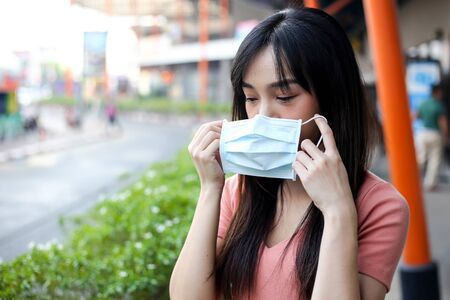Beautiful asia woman wearing mouth mask against air smog pollution PM 2.5