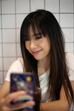 close up of beautiful asia woman smile and take a selfie by smart phone in restaurant.