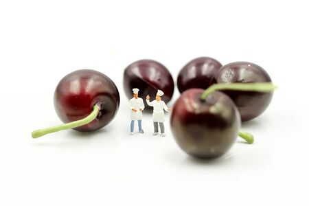Miniature people : chef with cherrys,cherry month concept.