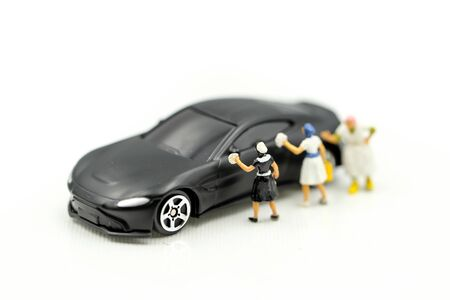 Miniature people: Worker cleaning car using as  business concept. Zdjęcie Seryjne