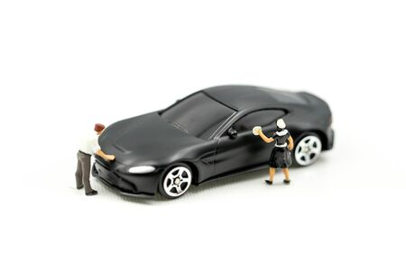 Miniature people: Worker cleaning car using as business concept.