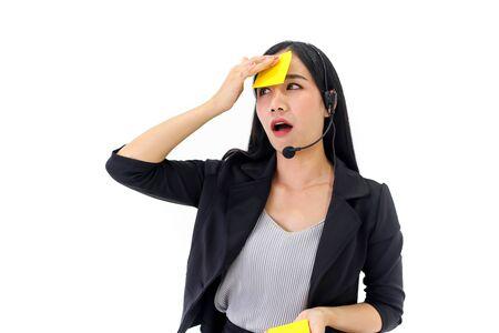 Beautiful asian woman Serious call center operator in wireless headset talking with customer Standard-Bild