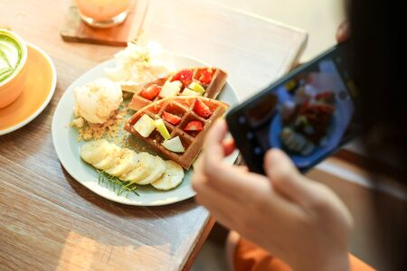 Asia beautiful woman taking photo on her waffles in the coffee shop and prepared to upload to a social app. Stock Photo